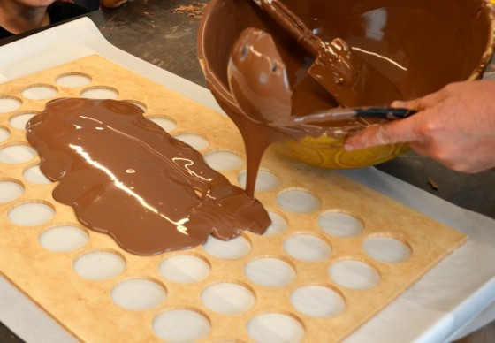 pouring the chocolate into the freckle molds