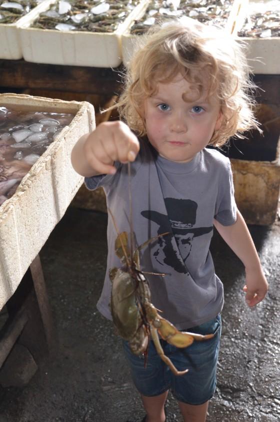 JImbaran bay with kids - a small boy and a crab at Jimbaran Fish Markets