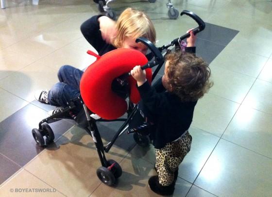 toddler pushing her big brother in pram