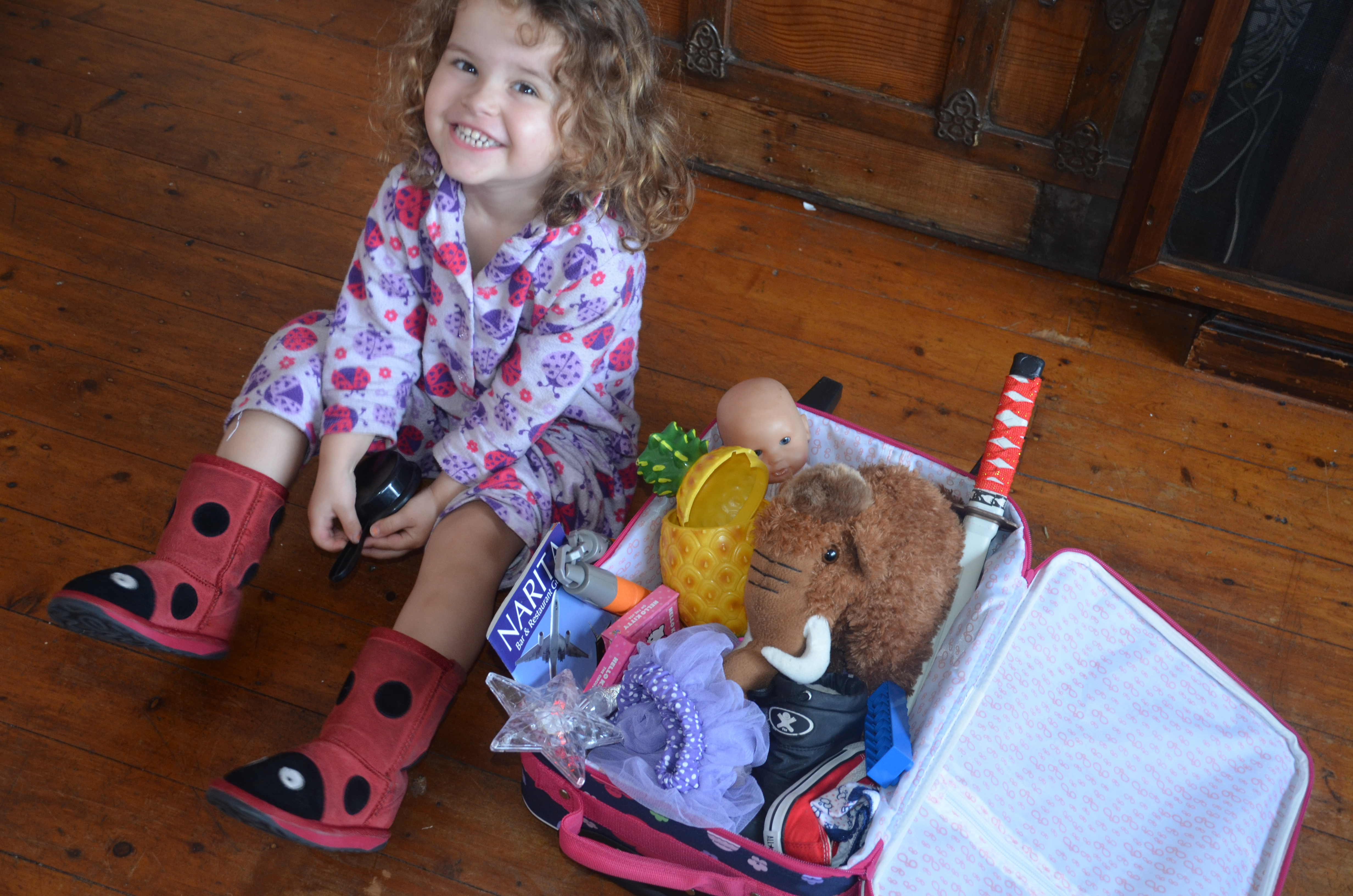 little girl packing her own luggage