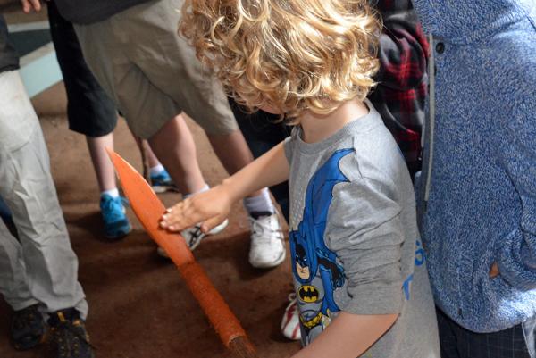 applying ochre resin to a spear at Blak Markets