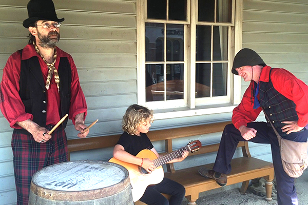 Young boy playing guitar with old time performers at Sovereign Hill