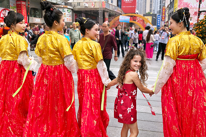 Little girl with traditionally costumed ladies in Guangzhou