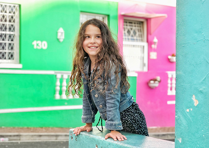 Little girl looking at brightly coloured houses in Bo Kaap Cape Town