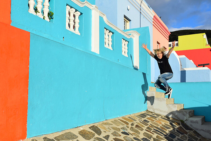 Kid jumping for joy outside a blue house in Bo Kaap