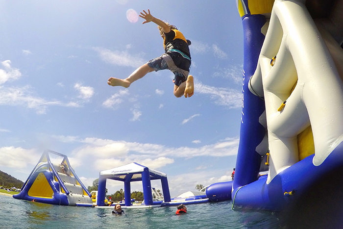 Boy leaping off the inflatable onstacle course at Stoney Aqua Park with kids