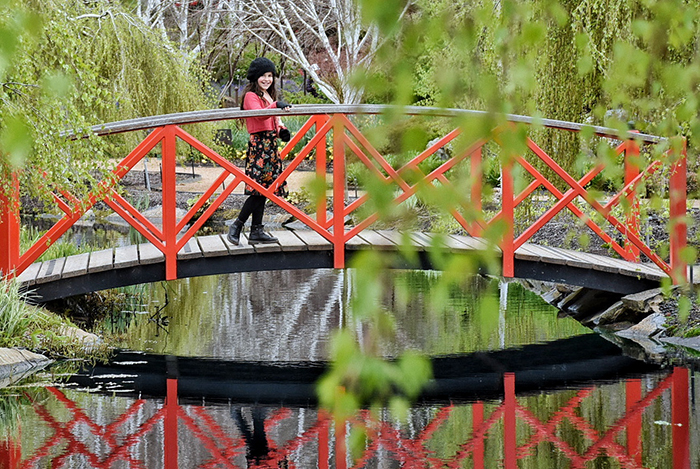 Little girl wearing red and back at Chinese gardens at Mayfield Garden in Oberon