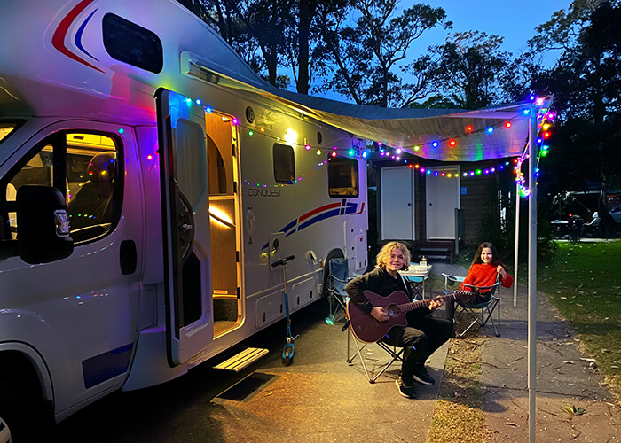 Boy playing guitar under fairy lights by a motorhome